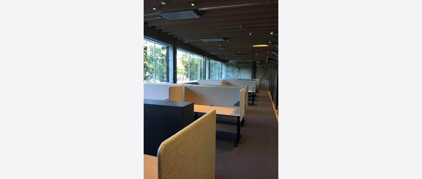 Alle pulter, skap og samtlige møtebord er spesialtegnet. Møtebordene har røffe råstålrammer og delikate eiketopper. Foto: Asplan Viak