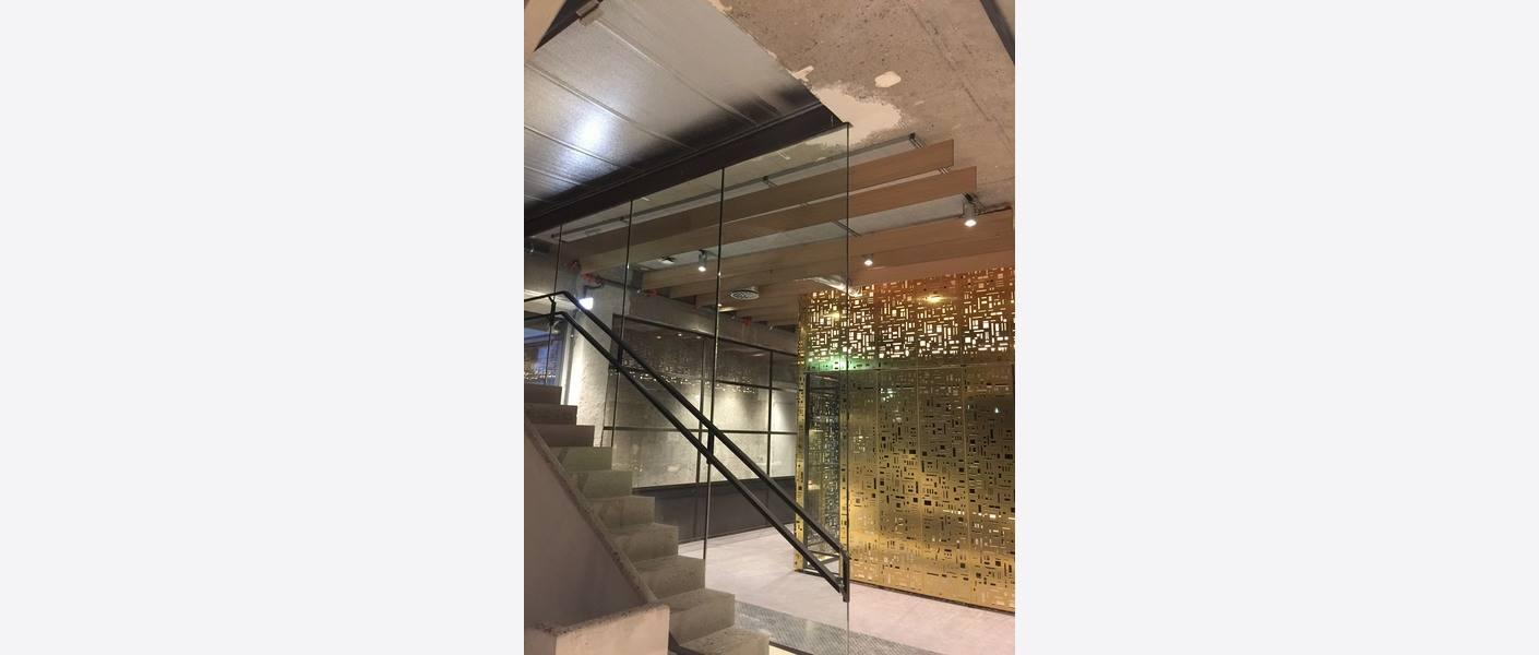 Plasstøpt betongtrapp og nedhengte trebafler som himling for å kompensere for klanglyd. Foto: Asplan Viak