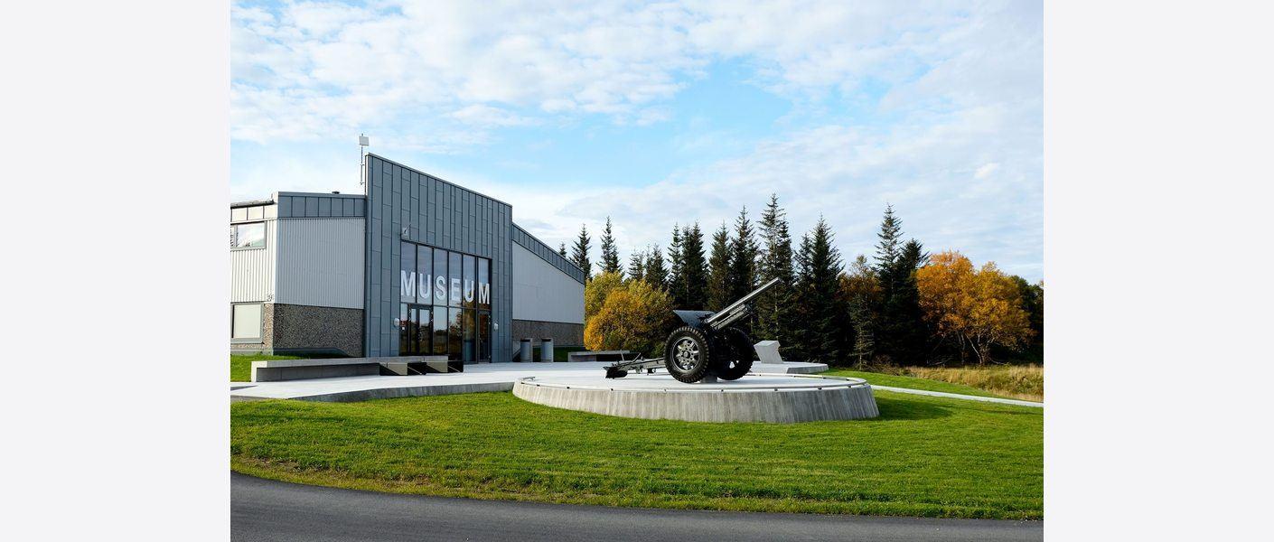 Museumsbygningen med forplass og landskap. Museet er etablert i en ombygd industribygning. Museets forplass og anlegget er presist, enkelt og nøkternt formgitt, inspirert av kystfortets rå og funksjonelle form. Foto: Asplan Viak