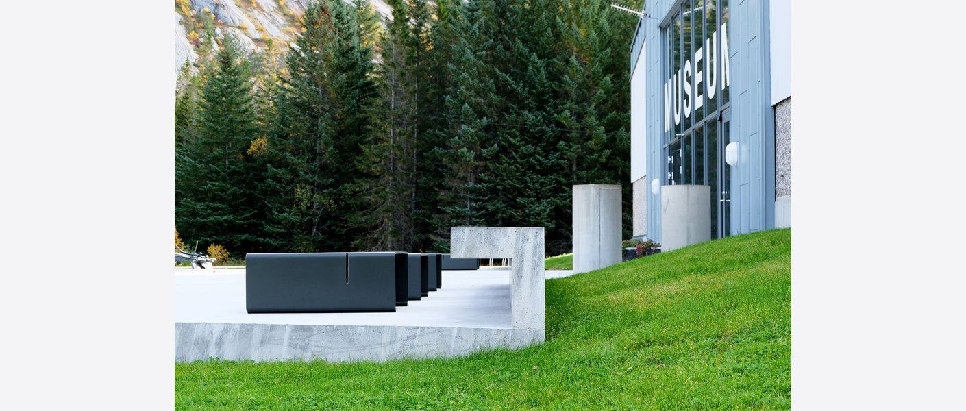 Forplassens avslutning mot fasaden er formet som en lang benk. Like ved finner man lave bord i stål med samme farge som kanonen. Foto: Asplan Viak