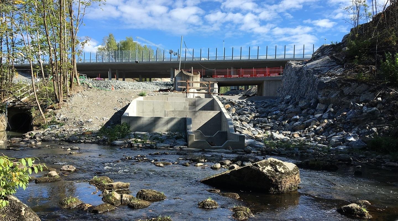 Åpning av Dælibekken i forbindelse med utbedring av E16 Bærum. Etablering av faunapassasje og flomløp ved utløp til Sandvikselva. Under bygging